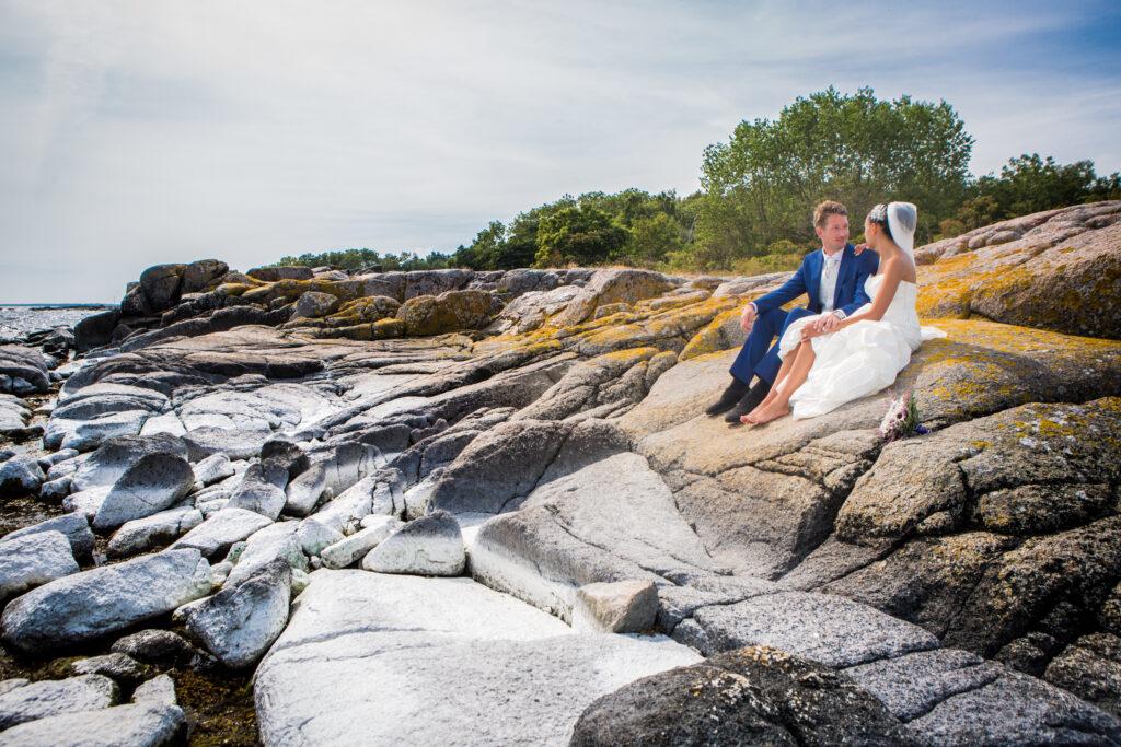 Hochzeitspaar sitzt auf den Felsen